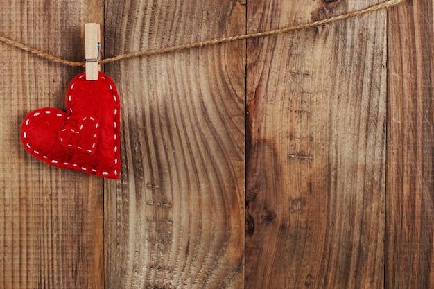Corações vermelhos são mantidos por prendedores de roupa na corda de juta, em madeira escura. copie o espaço