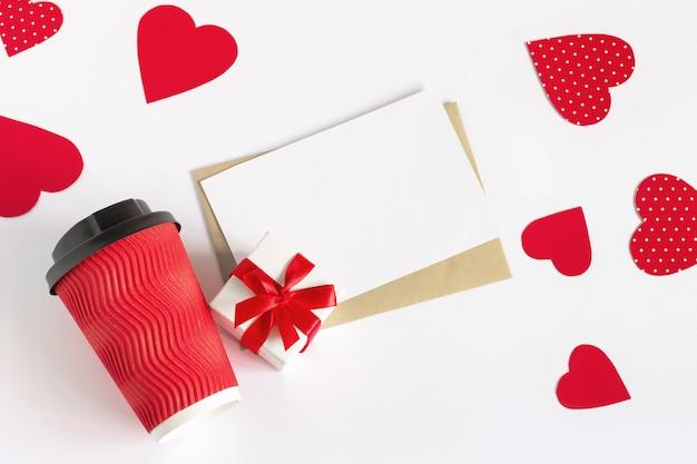 Corações vermelhos, uma xícara de café vermelha, uma caixa de presente, uma folha de papel branca e uma carta