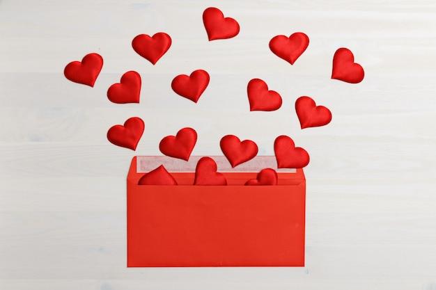 Corações voando fora de um envelope de papel vermelho
