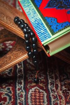 Corão colorido com rosário na madeira