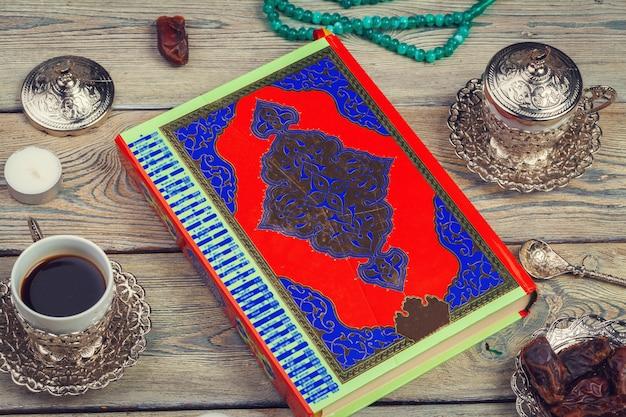 Corão colorido com rosário na superfície de madeira