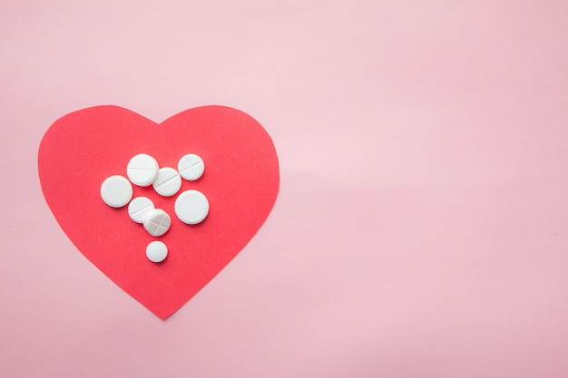 Corazon de papel com imagens de medicina no fundo rosa