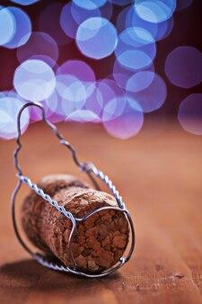 Corck para champanhe na mesa de madeira e turva