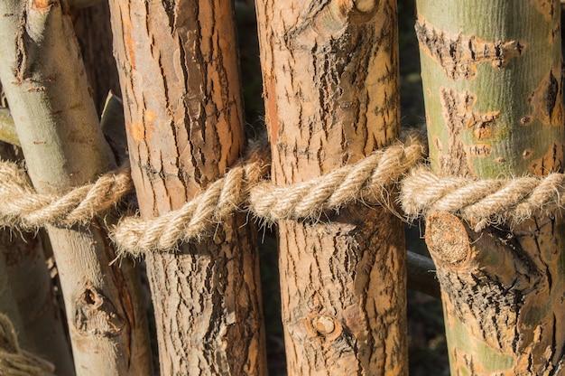 Corda amarrada em um nó em torno de postes de madeira, postes de vedação. fechar-se