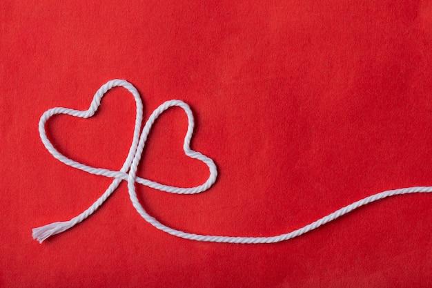 Corda branca em forma de dois corações sobre fundo vermelho. conceito de amor.