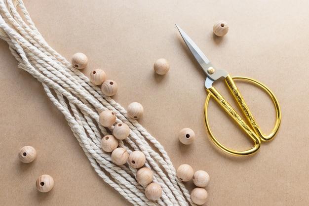 Corda de algodão bege para macramê, contas de madeira e tesoura em papel artesanal. tema feito à mão e artesanal. vista superior, configuração plana.