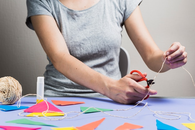 Corda de corte de mão de mulher com tesoura durante a confecção de estamenha