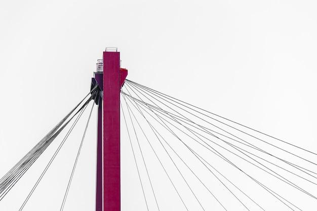Corda de metal presa ao poste de uma ponte estaiada