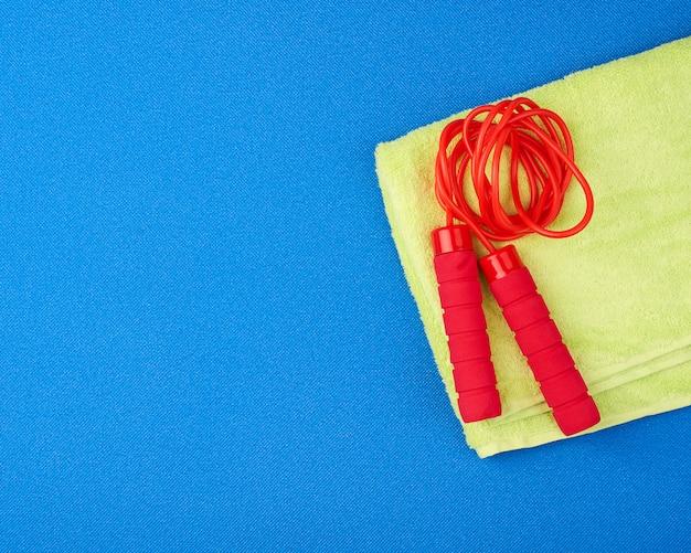 Corda de pular vermelha encontra-se em uma esteira de esportes azul neoprene