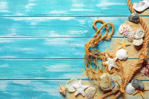 Corda do mar com muitas conchas do mar diferentes na areia do mar, sobre um fundo azul de madeira. vista do topo