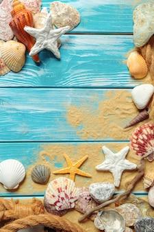 Corda do mar com muitas conchas do mar diferentes na areia do mar, sobre um fundo azul de madeira