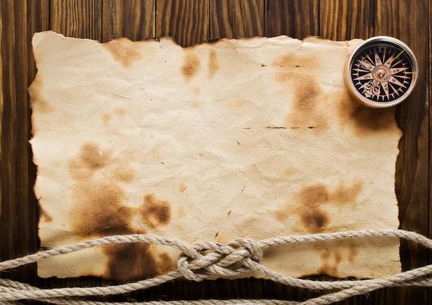 Corda e bússola na superfície de papel velho
