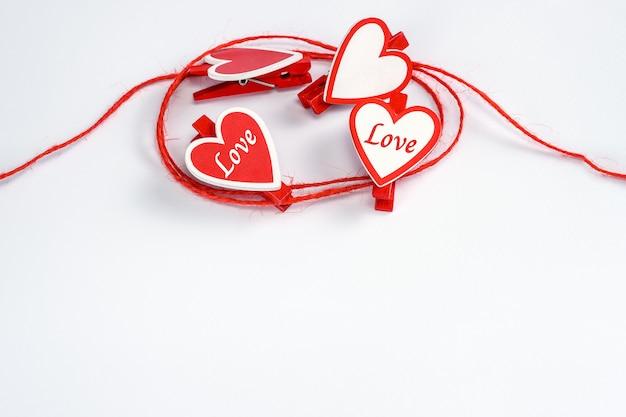 Corda enrolada com prendedores de roupa em forma de coração em um branco para dia dos namorados