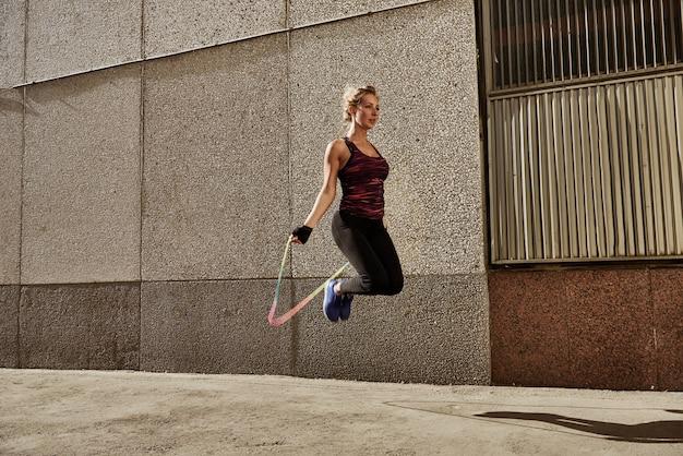 Corda nova da mulher da aptidão que salta contra a parede da cidade.