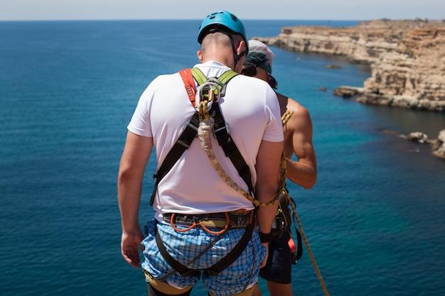 Corda pulando de um penhasco com uma corda na água. o oceano. mar. montanha.