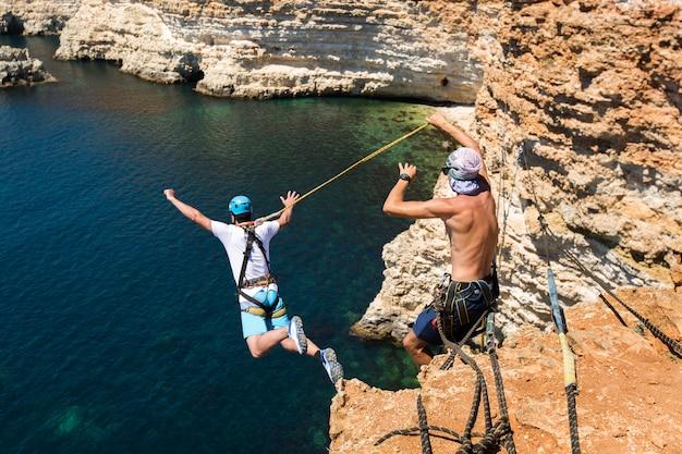Corda pulando de um penhasco com uma corda na água