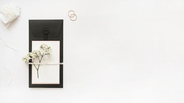 Cordas brancas; alianças de casamento e cartão com flores da respiração do bebê no fundo branco