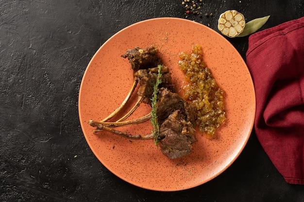 Cordeiro com osso com tomilho e cebola frita caramelizada. carré de cordeiro com cebola confitada, alho e pimenteiro em uma mesa preta. vista do topo.