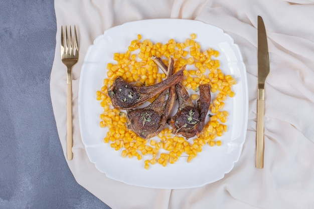Cordeiro mastiga na chapa branca com grãos cozidos e toalha de mesa de cetim no azul.