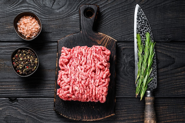 Cordeiro picado cru, carne moída com ervas e especiarias em uma tábua de madeira