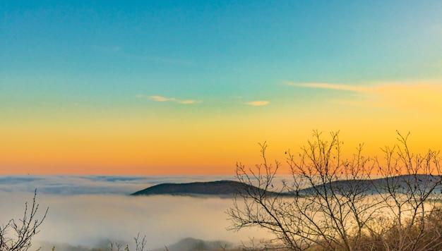 Cordilheira com silhuetas visíveis através da névoa colorida da manhã.