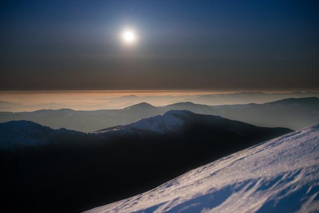 Cordilheira de montanhas de inverno na neve branca à noite, sob um céu azul escuro com lua e estrelas