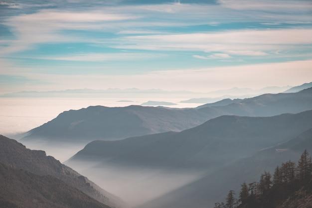 Cordilheira distante com neblina e névoa cobrindo os vales abaixo