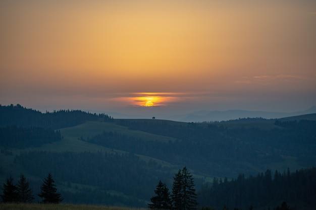 Cordilheira e prado ao pôr do sol com nuvens