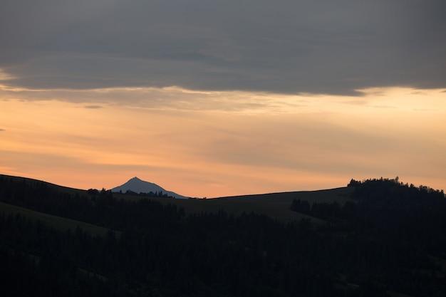 Cordilheira na superfície do céu do pôr do sol com nuvens