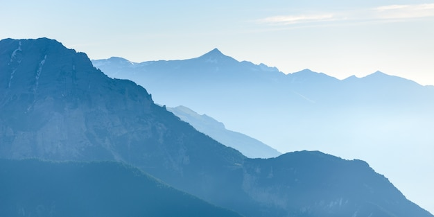 Cordilheira tonificada azul distante dos majestosos alpes europeus com névoa e nevoeiro no vale abaixo