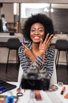 Cores brilhantes. mulher de pele escura usando muitos anéis demonstrando novas amostras brilhantes