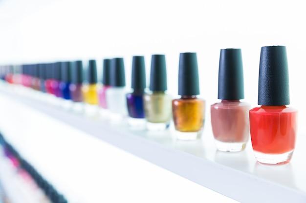 Cores de esmaltes coloridos em uma linha no salão de unhas em branco