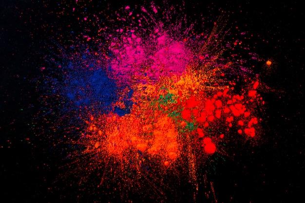 Cores de holi multicoloridas misturadas sobre fundo preto