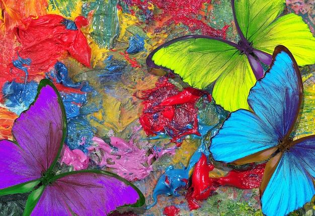 Cores do arco-íris. conceito de cor. borboletas morfo tropicais brilhantes na paleta de um artista. mesa colorida com pinturas artísticas e borboletas