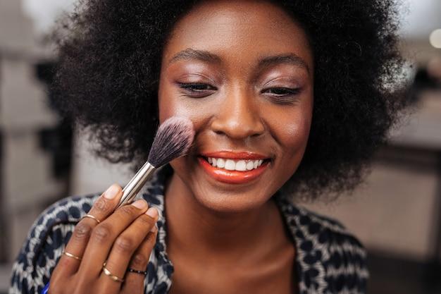 Cores lindas. mulher positiva de pele escura com cabelo encaracolado, fazendo um blush no rosto enquanto está sentada em frente ao espelho