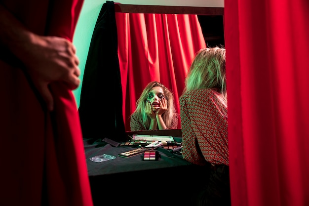 Coringa de halloween maquiagem olhando no espelho