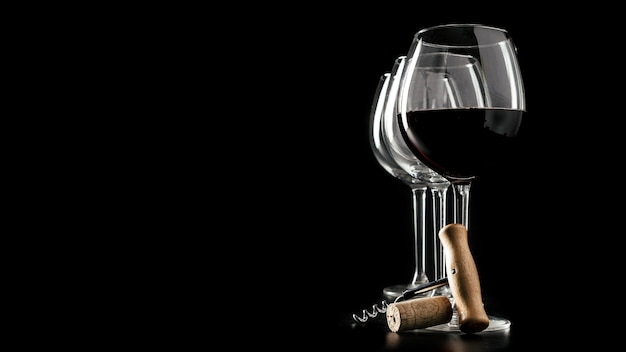 Corkscrew e cortiça perto de copos de vinho