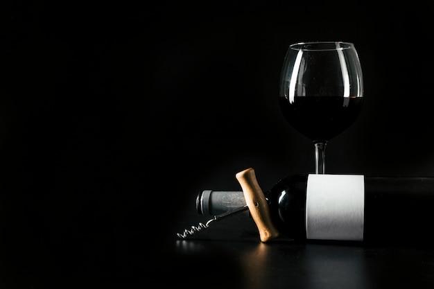 Corkscrew e garrafa perto de wineglass