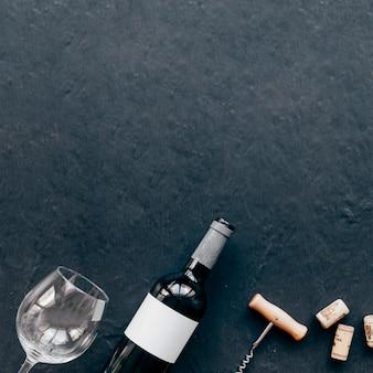 Corkscrew e vidro vazio perto da garrafa