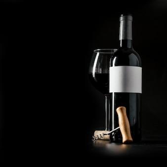 Corkscrew perto de garrafa e copo de vinho