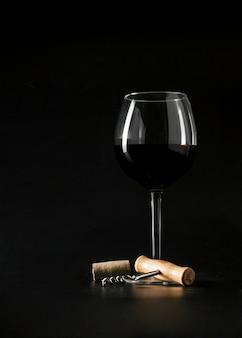 Corkscrew perto de um copo de vinho
