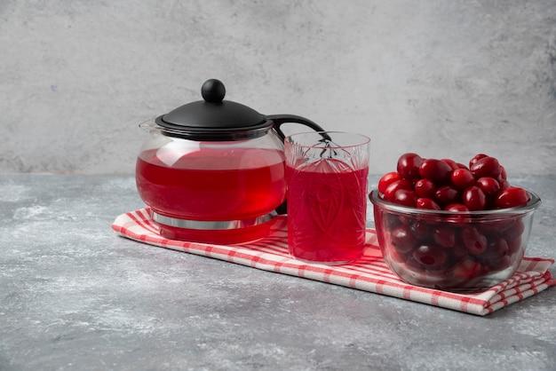Cornels e suco vermelho em copos e chaleira.
