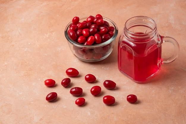 Cornels vermelhos em copo de vidro com suco na jarra.