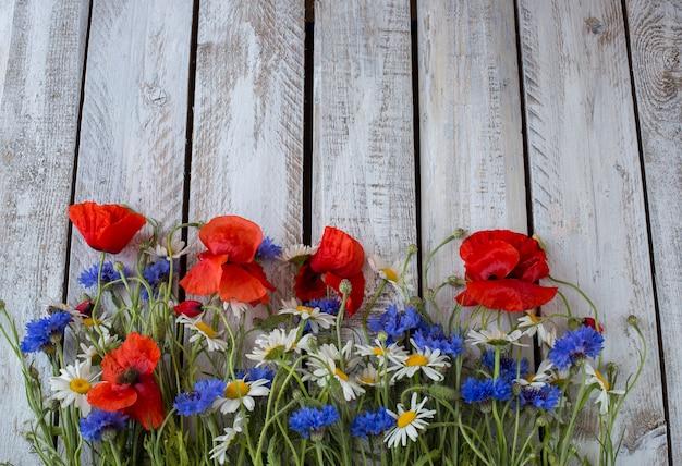 Cornflowers, camomila, papoulas sobre uma mesa de madeira branca