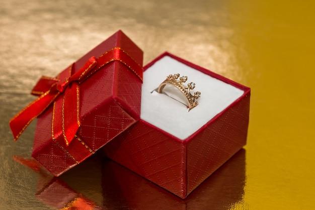 Coroa de anel de ouro em caixa de presente vermelha
