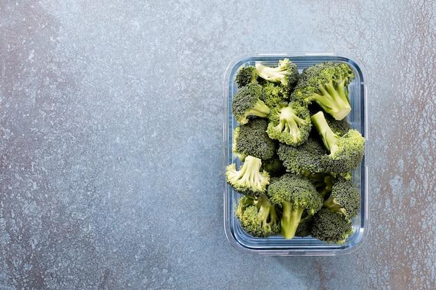 Coroa de brócolis lavada e fatiada em recipiente de vidro brócolis orgânico, cortado e pronto para ser usado na culinária