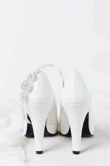 Coroa de diamante sobre o par de saltos altos de casamento branco contra o pano de fundo branco