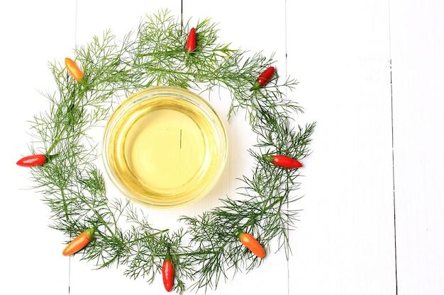 Coroa de especiarias, endro, pimenta e azeite de oliva em um fundo de madeira branco estilo vista superior plana de uma moldura redonda