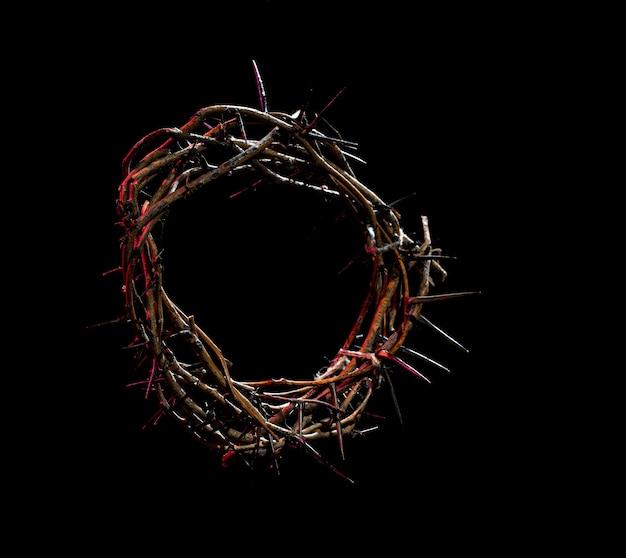Coroa de espinhos com tonalidade vermelha clara no escuro. o conceito de semana santa, sofrimento e crucificação de jesus.