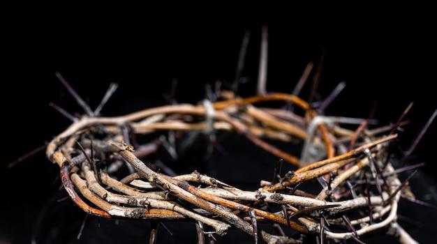 Coroa de espinhos no escuro close-up. o conceito de semana santa, sofrimento e crucificação de jesus.